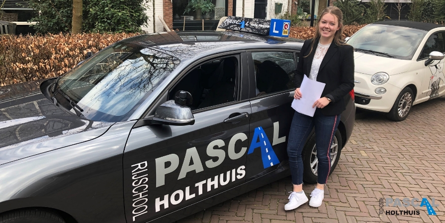 Mathilde, vrolijk naast de lesauto van Rijschool Pascal Holthuis