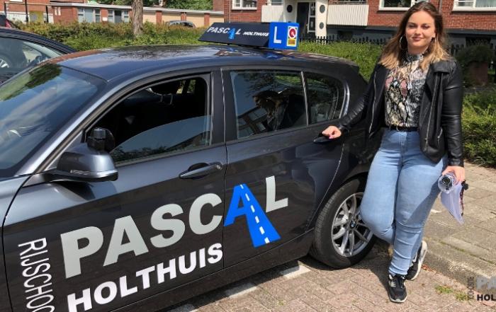 Foto van Francisca naast de auto van Rijschool Pascal Holthuis