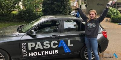Foto van Merel juichend naast de lesauto van Pascal Holthuis