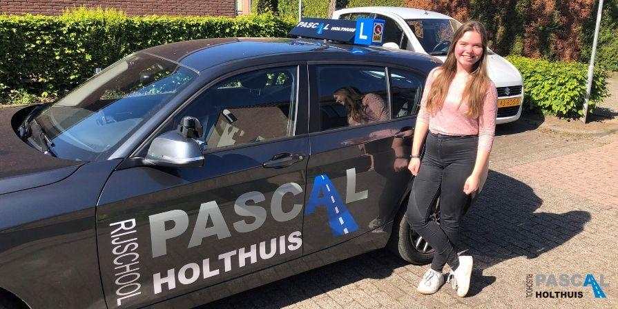 Robin naast de auto van Rijschool Pascal Holthuis