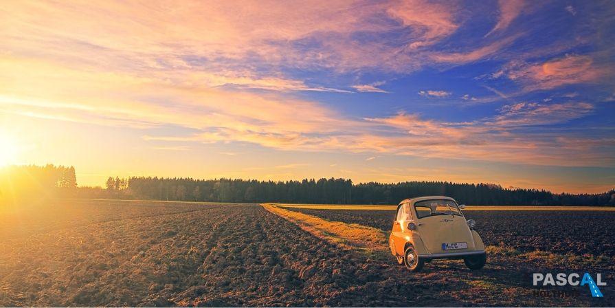 Een kleine auto in een weiland met zonsondergang