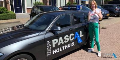 Maartje naast de auto van Pascal Holthuis met haar duimen omhoog
