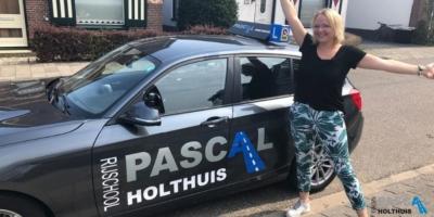 Anne naast de auto van Rijschool Pascal Holthuis