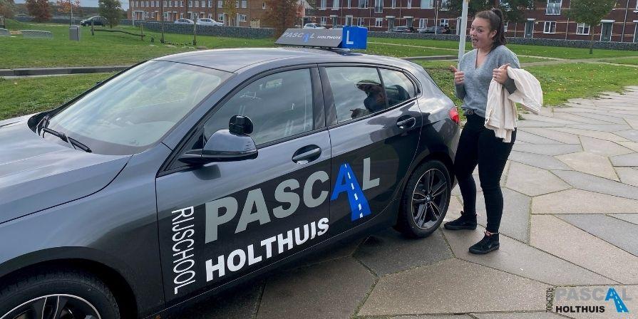 Noa naast de auto van Rijschool Pascal Holthuis
